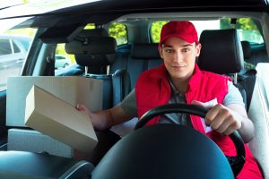 Delivery service worker in uniform delivering parcels and sitting at car. Man holding box, smiling and looking at camera